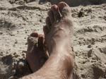 Ett par fötter i den varma sanden.